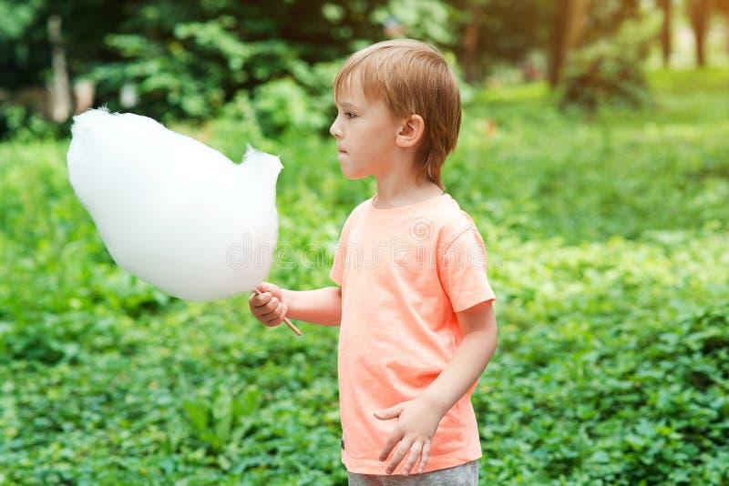 Peu garçon mangeant la sucrerie de coton au parc Vacances d'été Enfant heureux avec la sucrerie de coton douce Jour d'été ensolei photos libres de droits