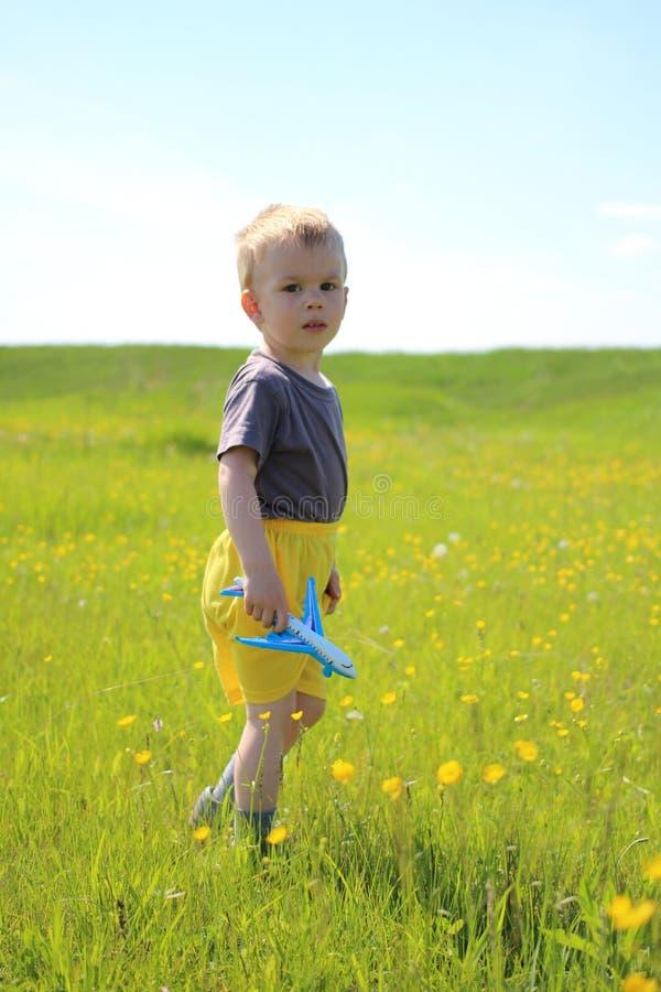 Peu garçon marchant dans le pré avec un avion de jouet photos stock