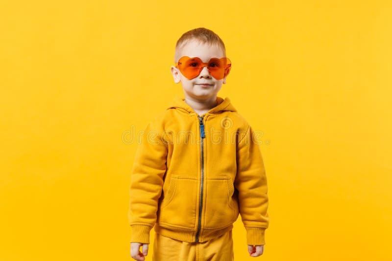 Peu garçon mignon d'enfant 3-4 années portant les vêtements jaunes d'isolement sur le fond orange lumineux de mur, studio d'enfan photo stock