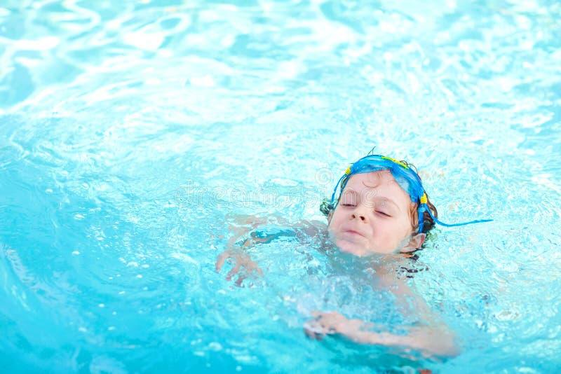 Peu garçon préscolaire d'enfant faisant le sport de concurrence de bain Enfant avec les lunettes de natation atteignant le bord d photo libre de droits