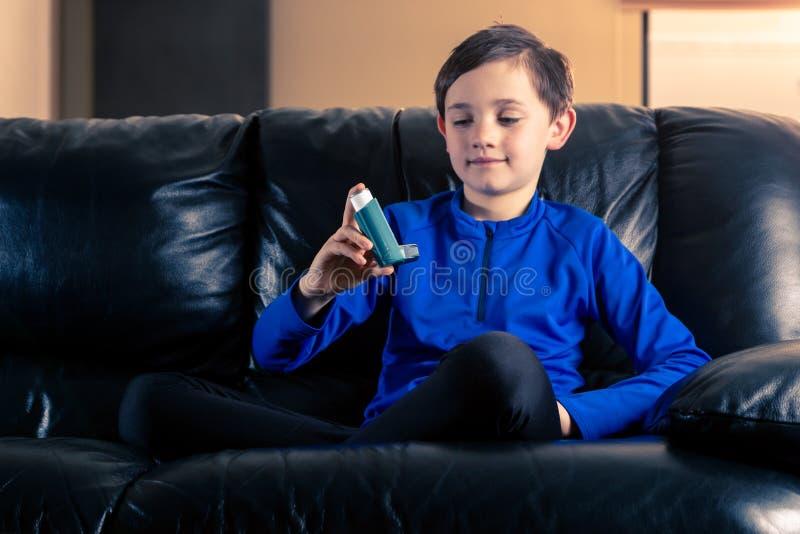 Peu garçon regardant l'inhalateur d'asthme photo stock