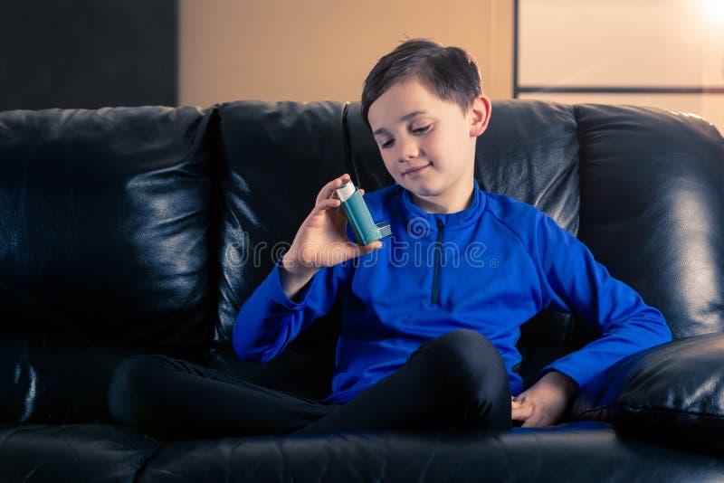 Peu garçon regardant l'inhalateur d'asthme images libres de droits