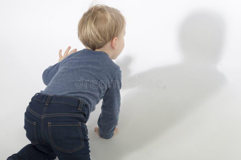Peu garçon regardant son ombre à l'arrière-plan blanc avec la lumière dure Projectile de studio Copiez l'espace photos libres de droits