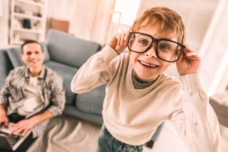 Peu garçon s'amusant en portant les lunettes de la lecture de son père photographie stock libre de droits