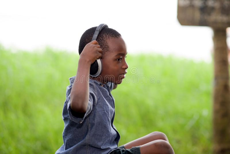 Peu garçon s'asseyant et écoutant la musique avec des écouteurs image libre de droits