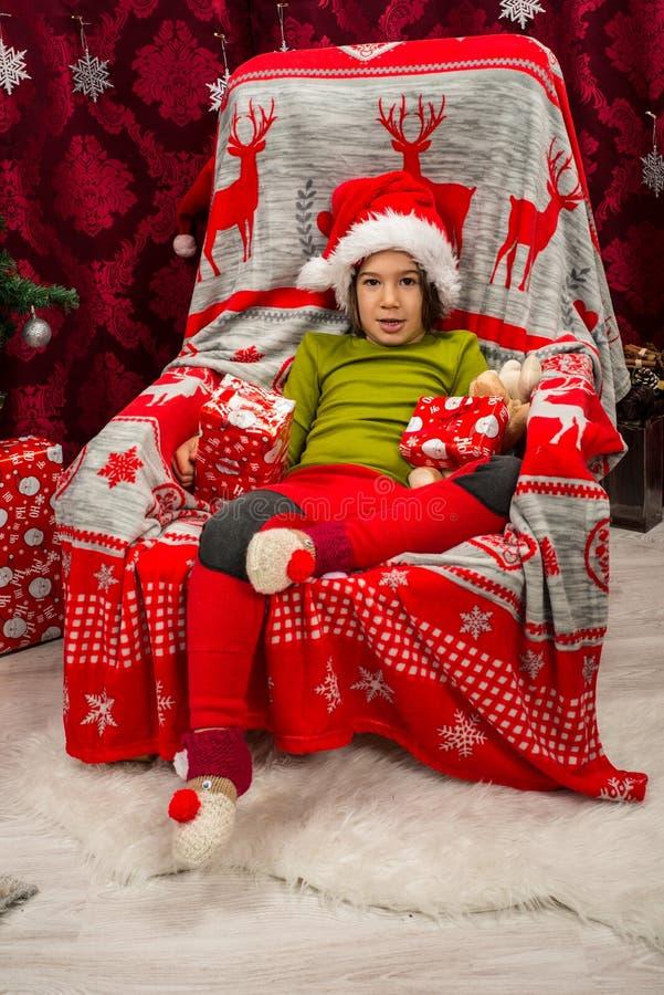 Peu garçon s'asseyant sur la chaise près de l'arbre de Noël photo stock