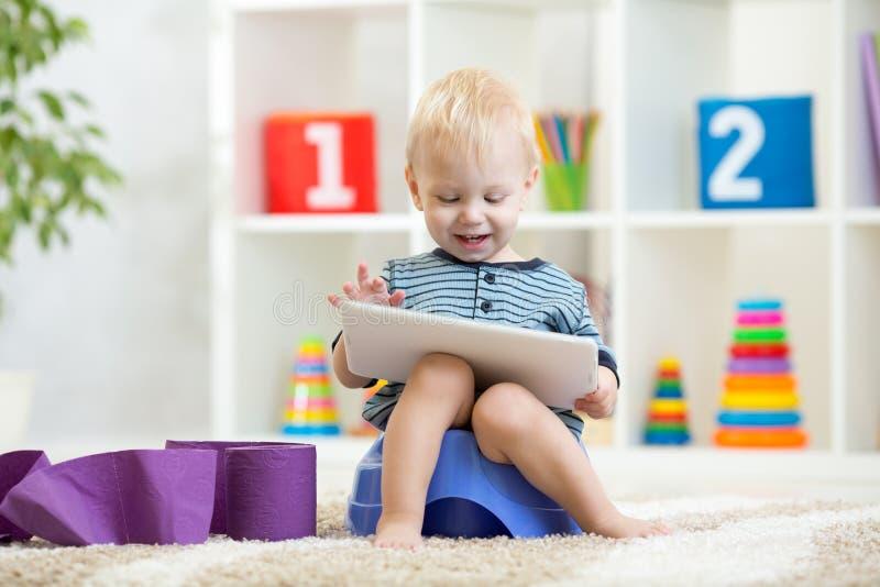 Peu garçon s'asseyant sur le pot et jouant avec le PC de comprimé image stock