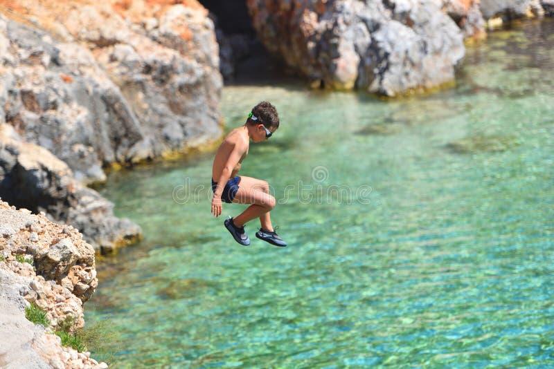 Peu garçon sautant outre de la falaise dans l'océan Mode de vie d'amusement d'?t? Gosse courageux photos stock