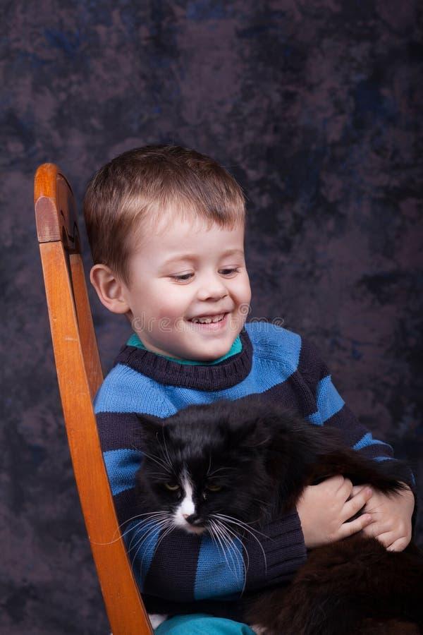Peu garçon tenant un grand chat noir photos stock