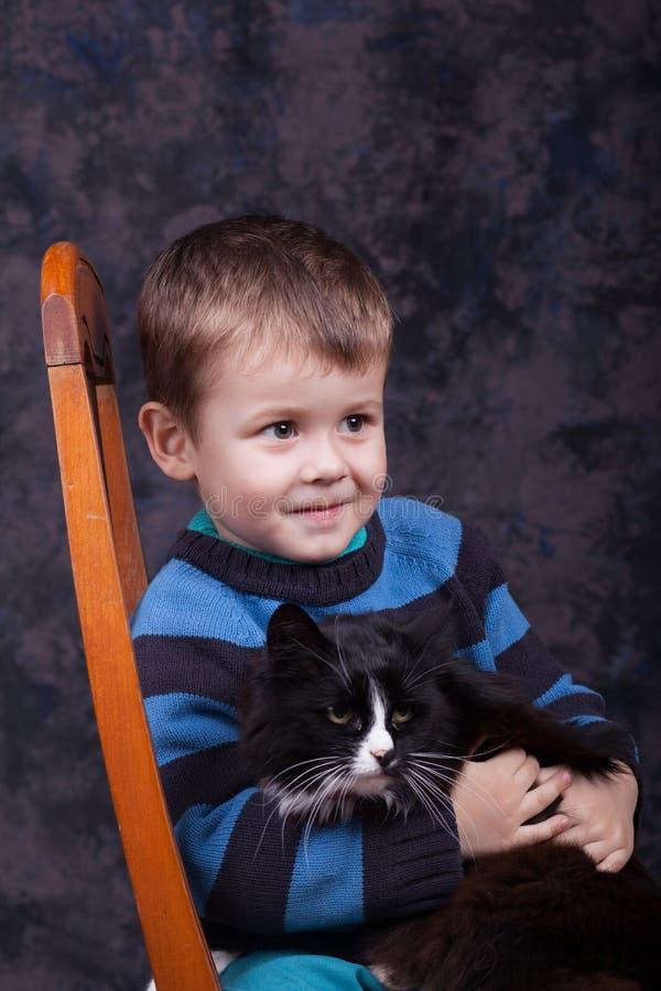 Peu garçon tenant un grand chat noir image stock