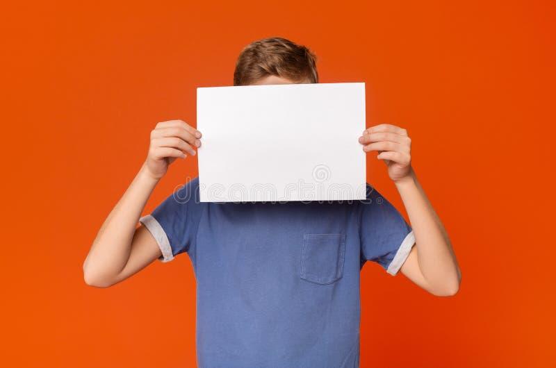Peu garçon tenant une carte vierge devant sa tête photographie stock libre de droits