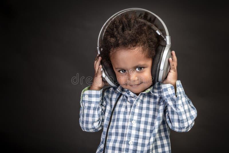 Peu garçon utilise de grands écouteurs photographie stock
