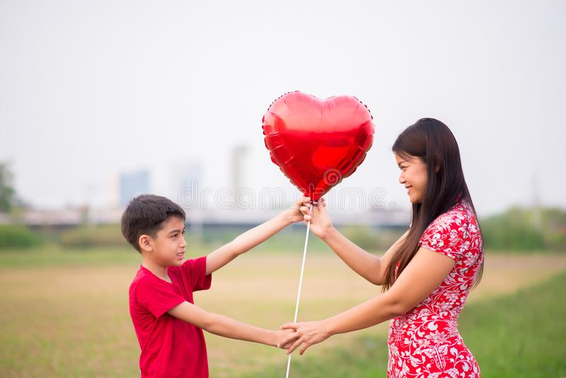 Peu garçons donnant le coeur de ballon à sa mère avec amour photos stock