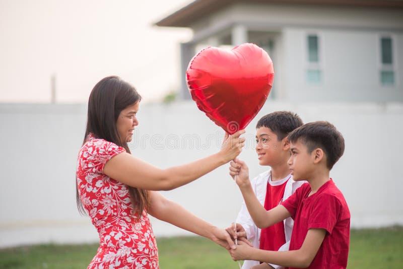 Peu garçons donnant le coeur de ballon à son amour maternel image libre de droits