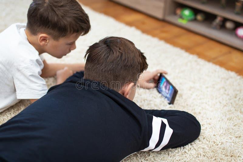 Peu garçons observant la vidéo par le smartphone sur le tapis photos stock