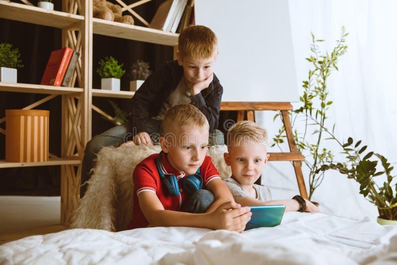 Peu garçons utilisant différents instruments à la maison photos libres de droits