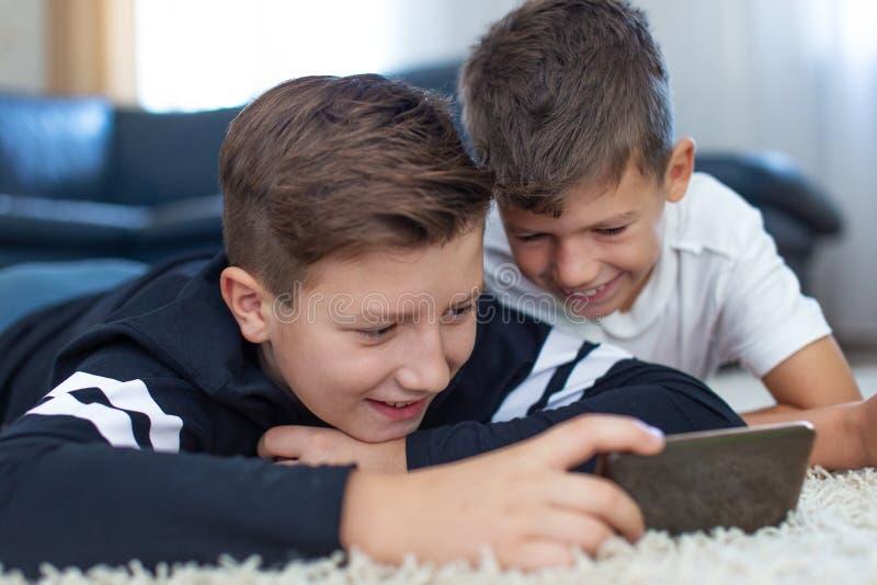 Peu garçons utilisant le smartphone sur le tapis et le sourire photos libres de droits