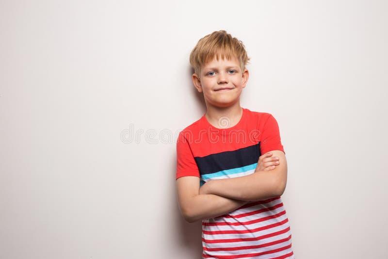 Peu gar?on de sourire dans le T-shirt d'isolement sur le fond blanc Portrait de studio images libres de droits