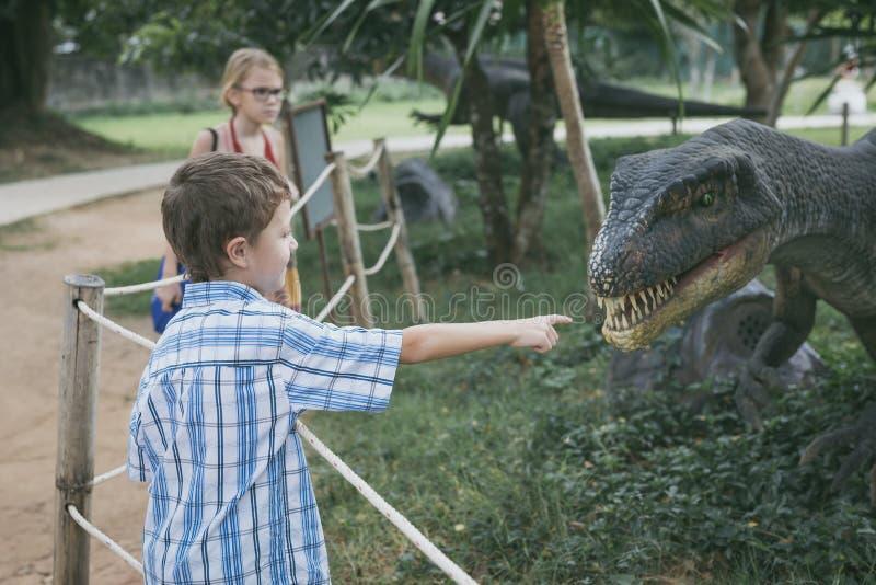 Peu gar?on jouant en parc de Dino d'aventure image stock