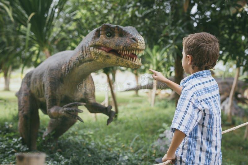 Peu gar?on jouant en parc de Dino d'aventure photo libre de droits