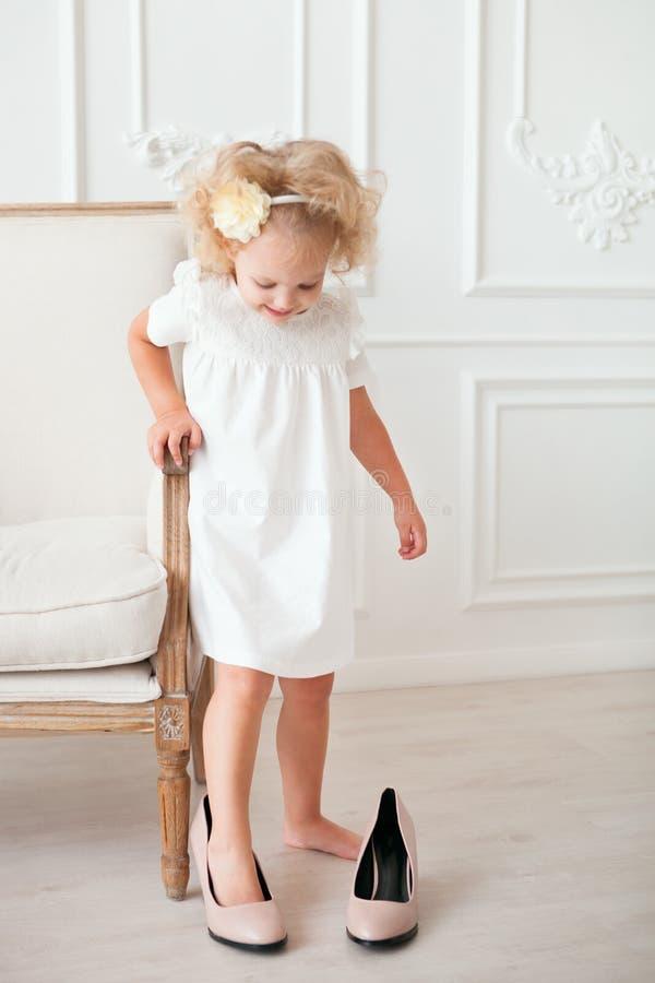 Peu jolie fille dans la robe blanche essayant sur les chaussures de la maman images stock