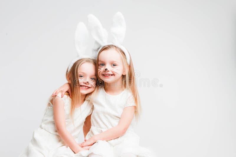Peu jumeaux blonds dans des robes blanches avec des oreilles de lapin Photo de studio sur le fond gris Les enfants c?l?brent P?qu photos libres de droits