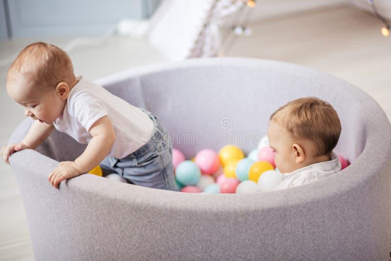 Peu les enfants mignons de sourire jouent avec des boules dans le puits de boule dans la chambre de jeu F?te d'anniversaire images libres de droits