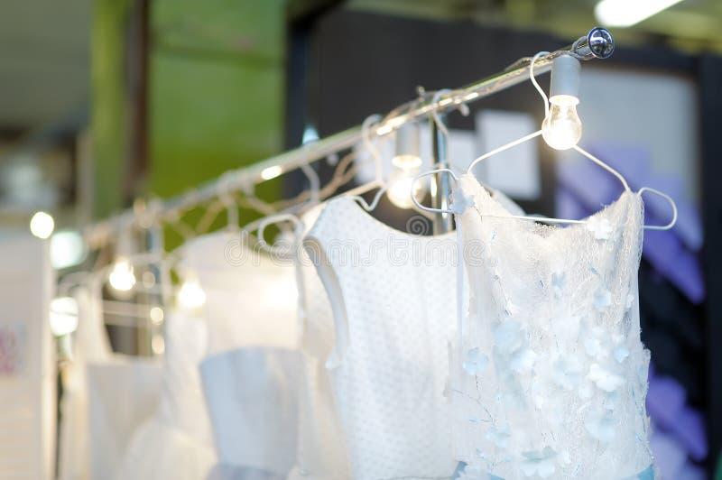 Peu mariage ?l?gant, demoiselle d'honneur, soir?e, robe de boule ou robes de bal d'?tudiants sur un cintre dans un magasin nuptia photo libre de droits