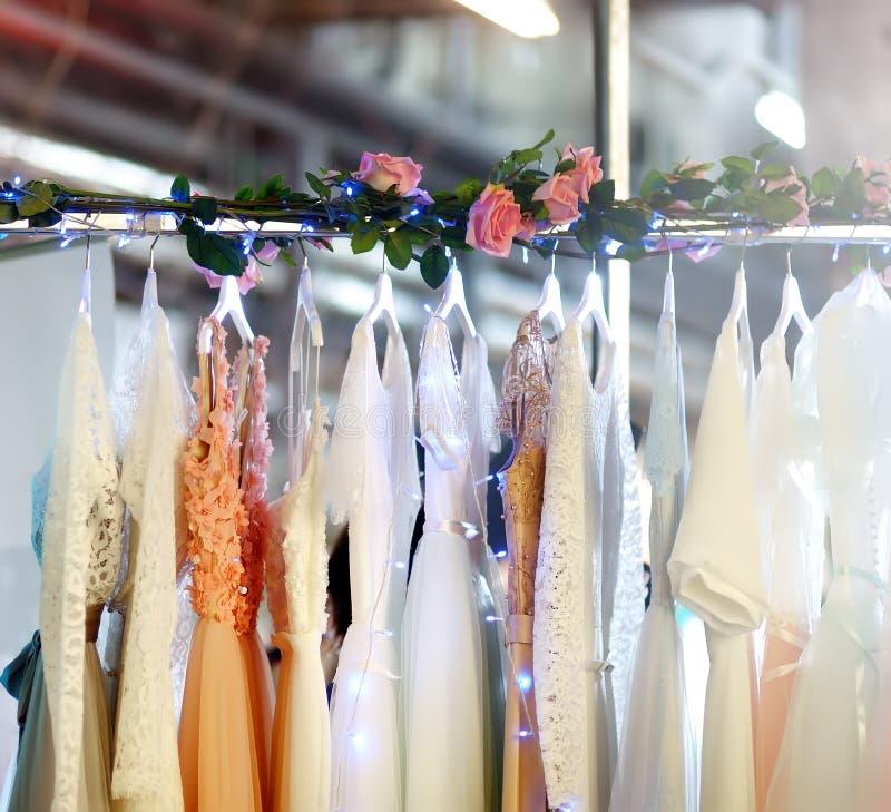 Peu mariage ?l?gant, demoiselle d'honneur, soir?e, robe de boule ou robes de bal d'?tudiants sur un cintre dans un magasin nuptia image libre de droits