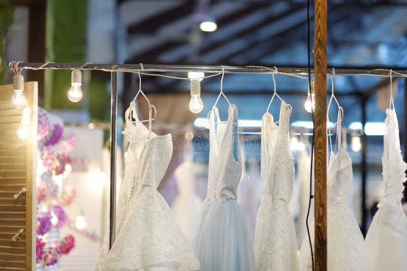 Peu mariage ?l?gant, demoiselle d'honneur, soir?e, robe de boule ou robes de bal d'?tudiants sur un cintre dans un magasin nuptia images stock