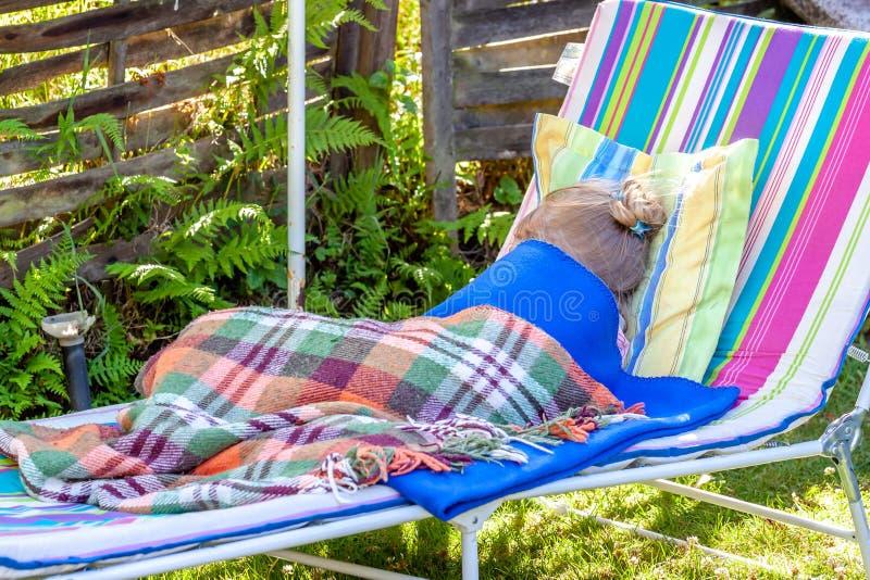 Peu mensonge de fille en difficulté dans le jardin sur le canapé du soleil images stock