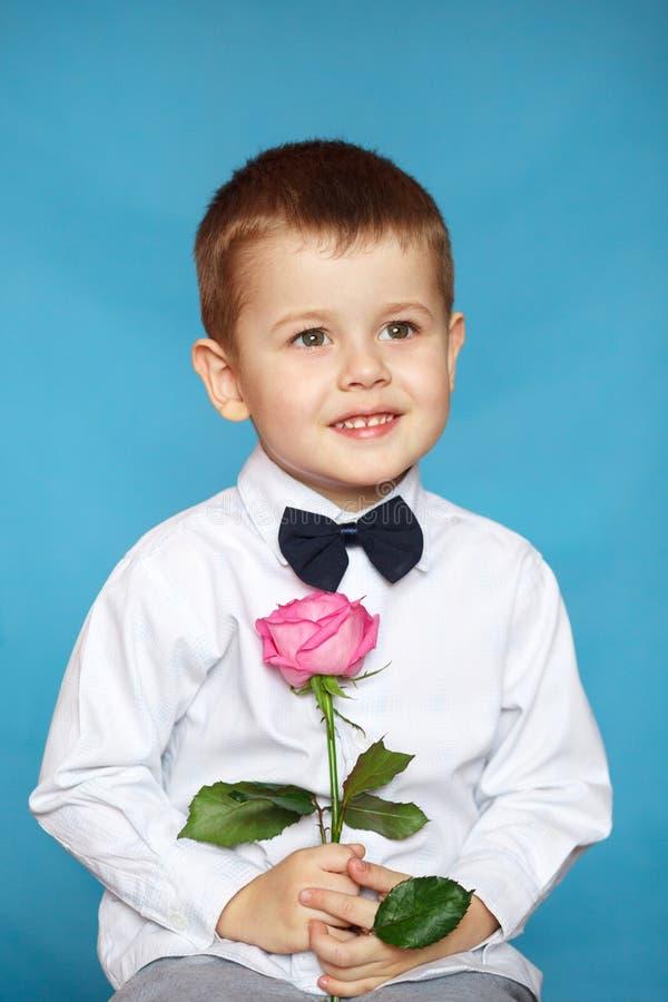 Peu monsieur tenant une rose rose D'isolement sur le fond bleu photographie stock