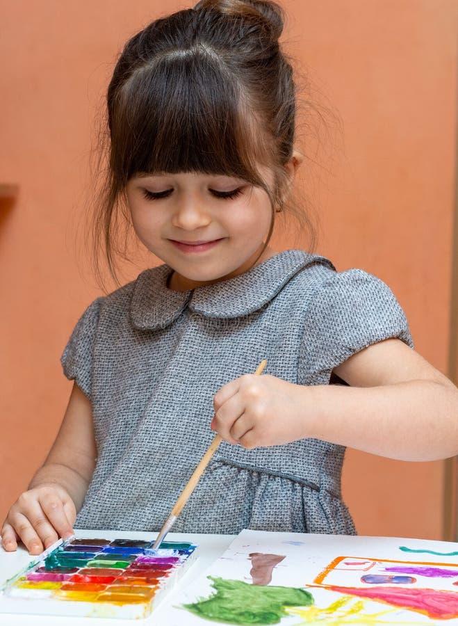 Peu peinture européenne de fille à la table à l'intérieur photographie stock libre de droits