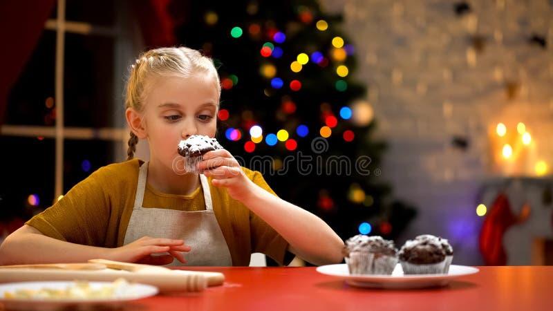 Peu petit pain de chocolat de reniflement de fille, humeur confortable de Noël, l'atmosphère de vacances image libre de droits