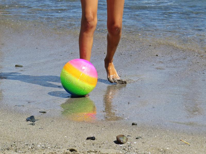 Peu petites jambes d'enfant dans l'eau sur Sandy Beach Relaxing et position avec la boule colorée pendant des vacances d'été photographie stock