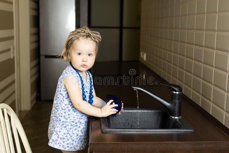 Peu plats de lavage de fille dans la cuisine à la maison photographie stock libre de droits