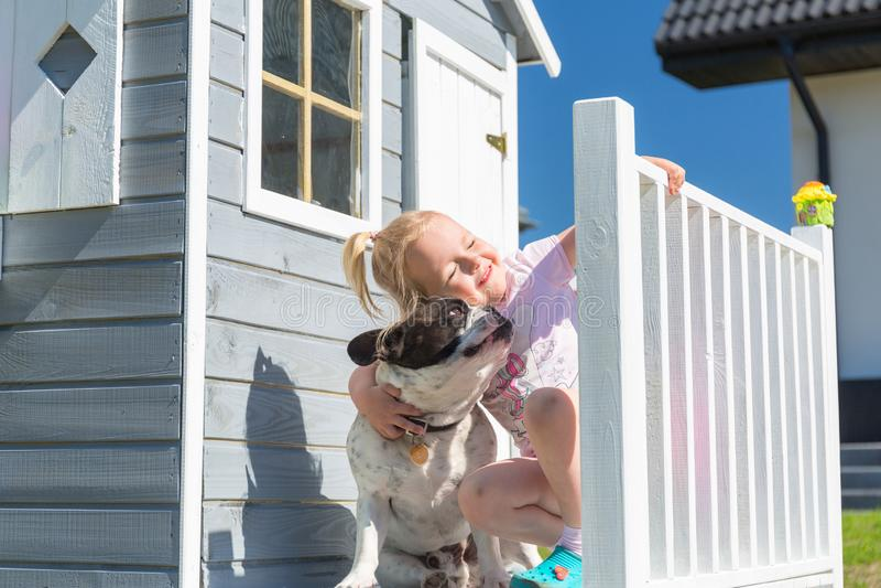 Peu portrait de fille avec le chien à la belle maison de jardin image stock