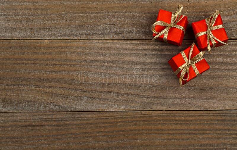 Peu présents rouges à la frontière en bois de Noël de fond photographie stock libre de droits