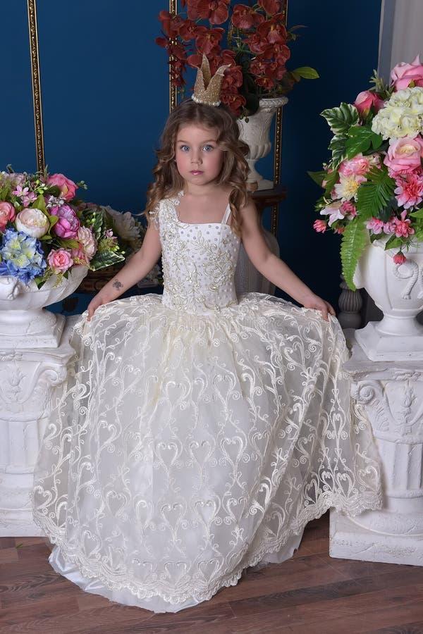 Peu princesse de fille dans une robe blanche et une couronne parmi des fleurs photos libres de droits