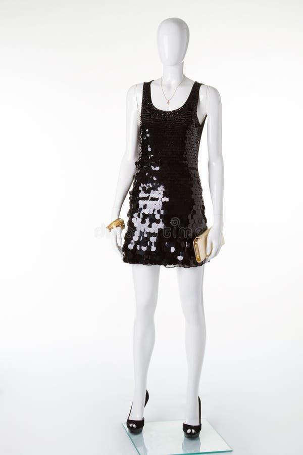 Peu robe noire avec les chaussures noires et un or pincent image libre de droits