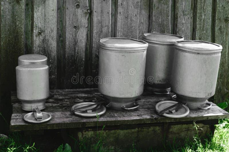 Peu séchant les boîtes métalliques lavées de lait en métal, barattes dans la campagne images libres de droits
