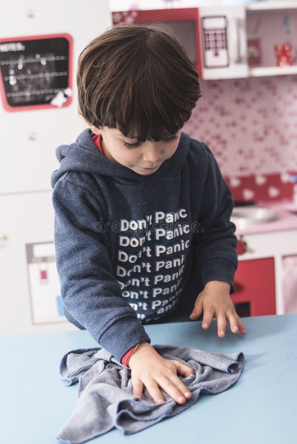 Peu table de nettoyage de bébé garçon avec le tissu image stock