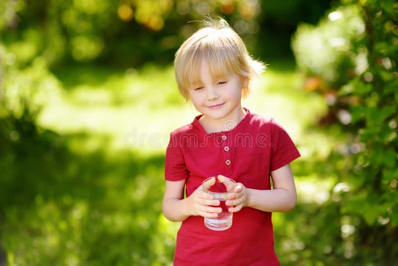 Peu verre à boire de garçon de l'eau dans le jour d'été ensoleillé chaud sur l'arrière-cour ou le jardin image stock