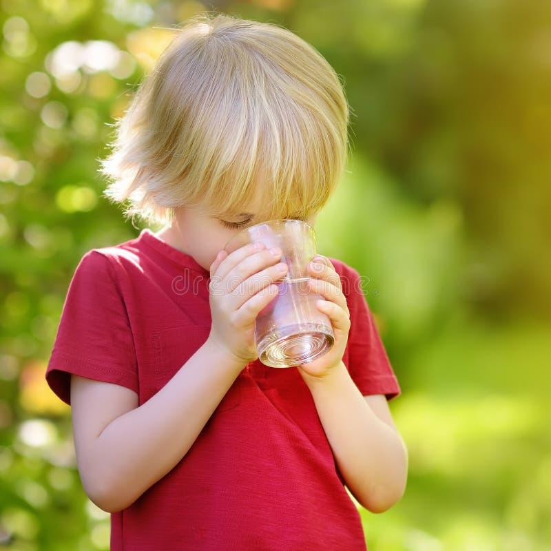 Peu verre à boire de garçon de l'eau dans le jour d'été ensoleillé chaud sur l'arrière-cour ou le jardin image libre de droits