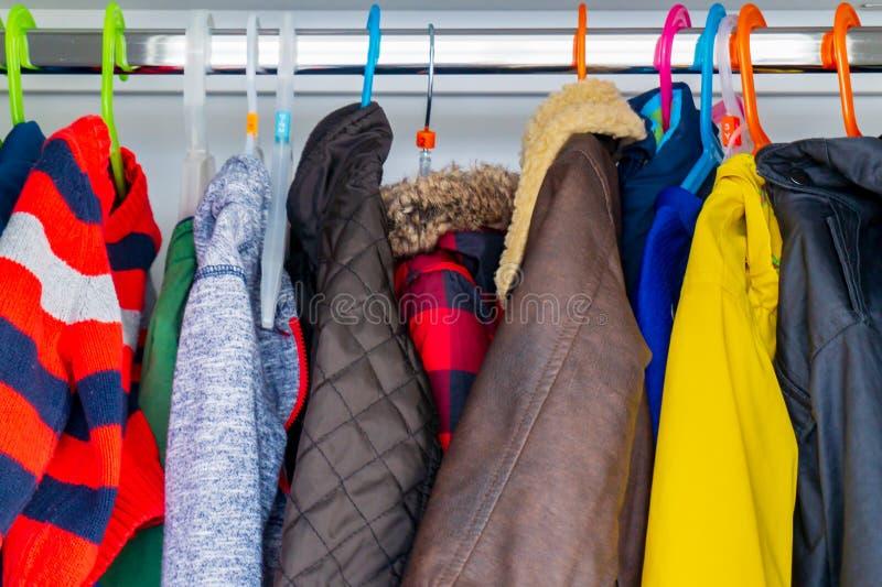 Peu vestes, manteaux et chandails de taille d'enfant de garçon accrochant dans le cabinet d'un enfant avec les cintres colorés photos stock