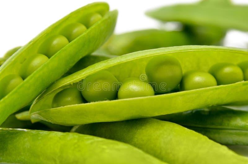 Peulen van groene die erwten op een witte achtergrond worden geïsoleerd Groene, rijpe, verse groenten peulvruchten royalty-vrije stock fotografie