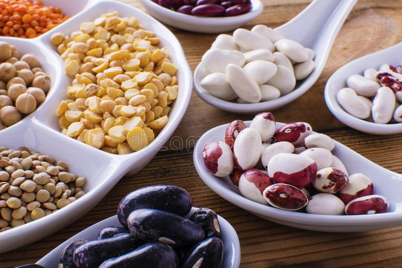 Peulvruchten, linzen, chikpea en bonenassortiment in verschillende kommen royalty-vrije stock foto's