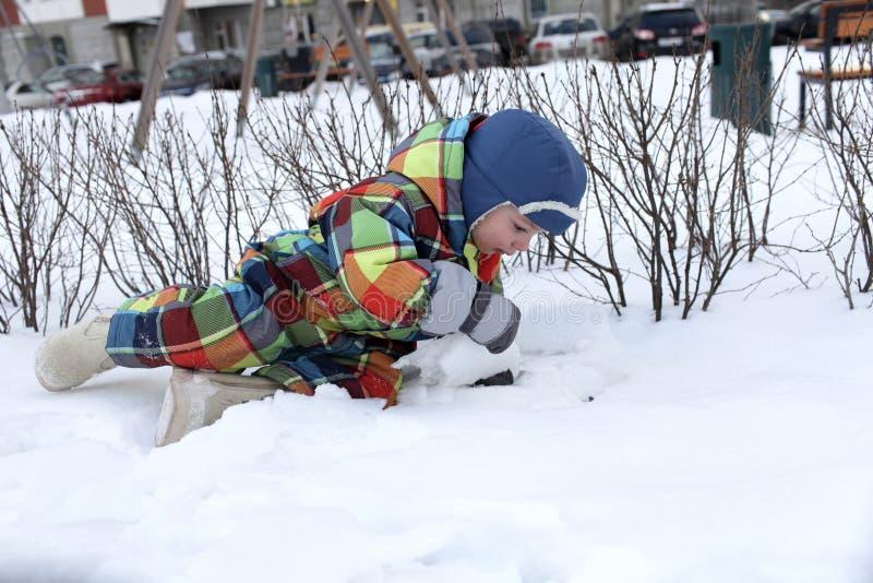 Peuter die in de sneeuw liggen stock foto's