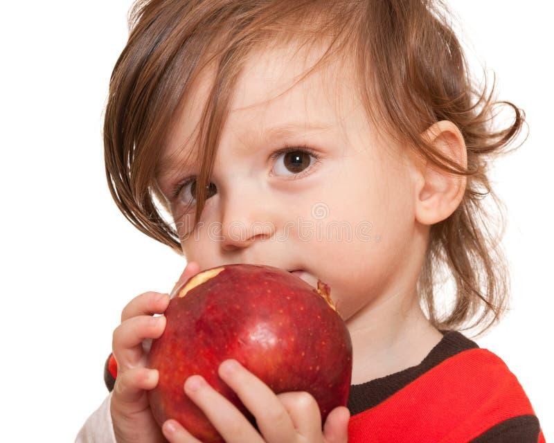 Peuter die een rode appel eet stock foto