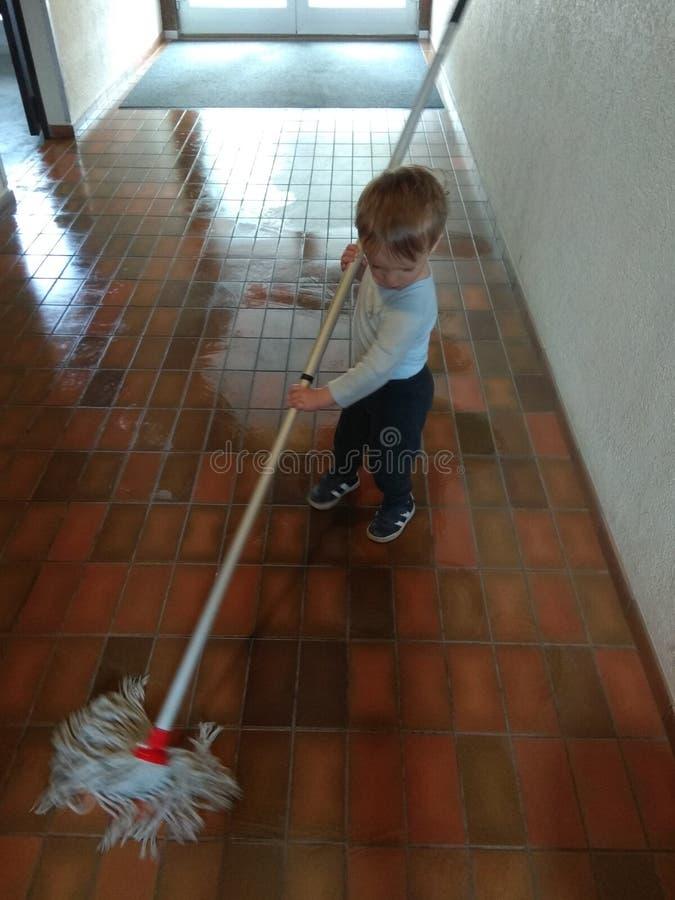 Peuter die helpen schoon te maken stock foto